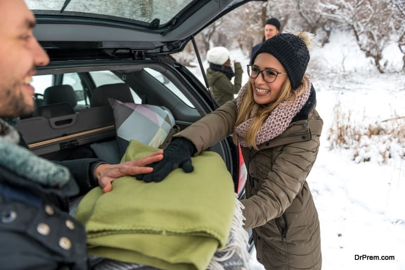 woman putting extra blankets in the car