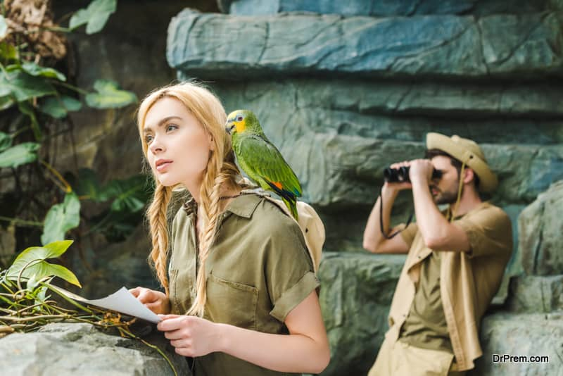 Beautiful young woman in safari suit with parrot and map navigating in jungle while her boyfriend