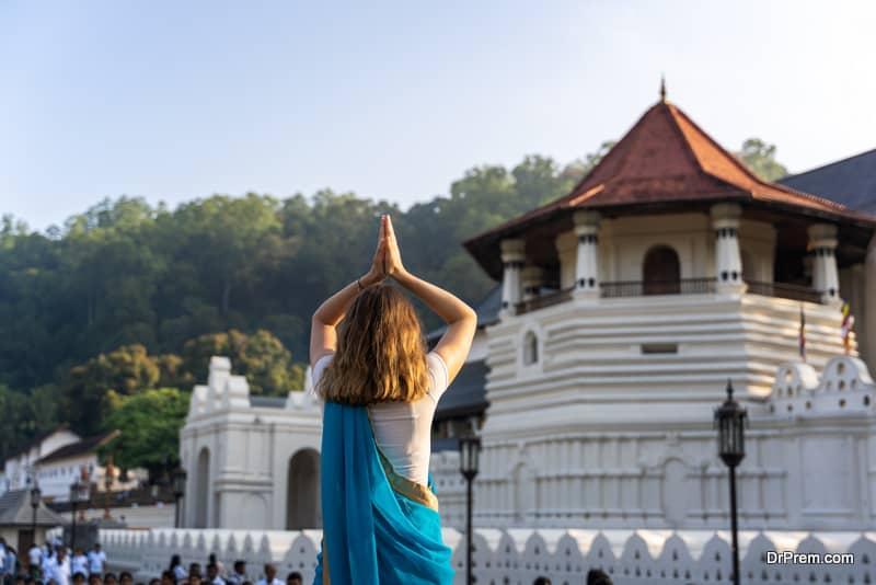 caucasian young woman is praying in front of Sri Dalada Maligwa temple