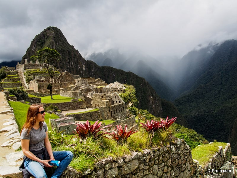 Cheerful-Woman-Sitting-at-Ancient-Stone-and-Looking-at-Machu-Picchu-Mountains