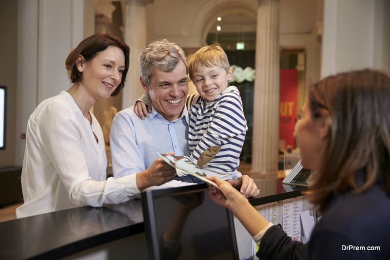 Family Buying Entry Tickets To Museum From Reception
