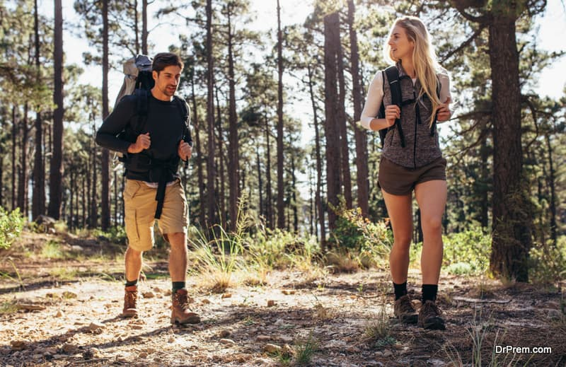 Man and woman hikers trekking on forest trail