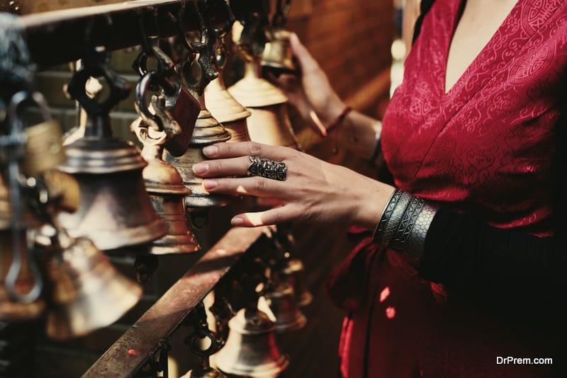 Woman hand touching buddhist bells in Nepali temple