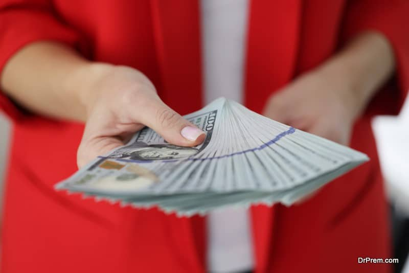 Woman in red jacket holding lot of American dollar bills in hands