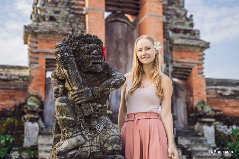 Young woman tourist in Traditional balinese hindu Temple Taman Ayun in Mengwi. Bali, Indonesia
