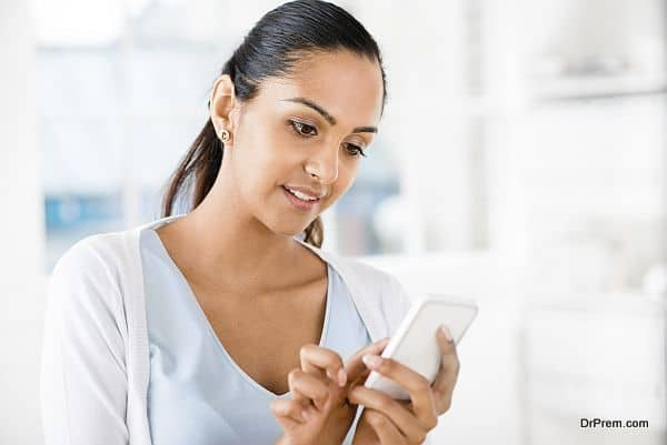 Beautiful Indian woman sending text message mobile phone happy