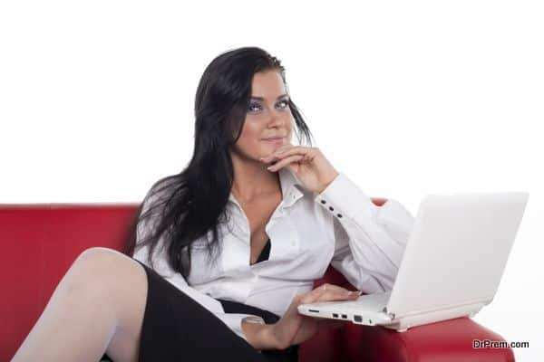 Attractive sexual woman with laptop on red sofa look at you