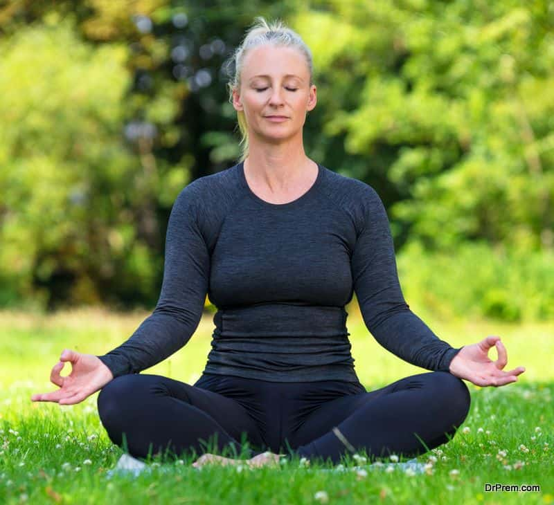 Mature middle aged fit healthy woman practicing yoga kapalbhati pranayama position