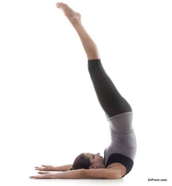 Sporty yoga girl on white background exercising standing on shoulders