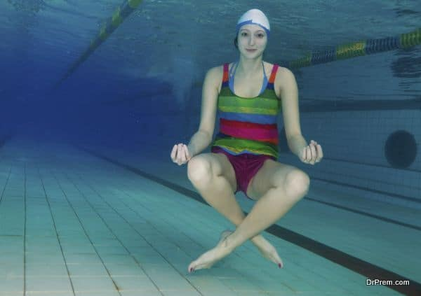 Girl sitting in yoga pose and meditating underwater