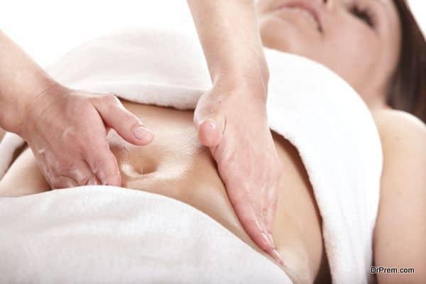 Girl having stomach massage. Body care.
