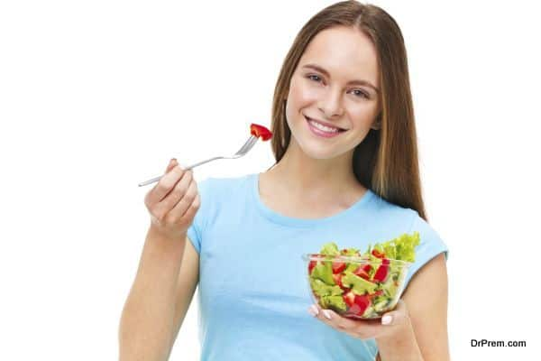 Portrait of a fit healthy woman eating a fresh salad isolated on white background.