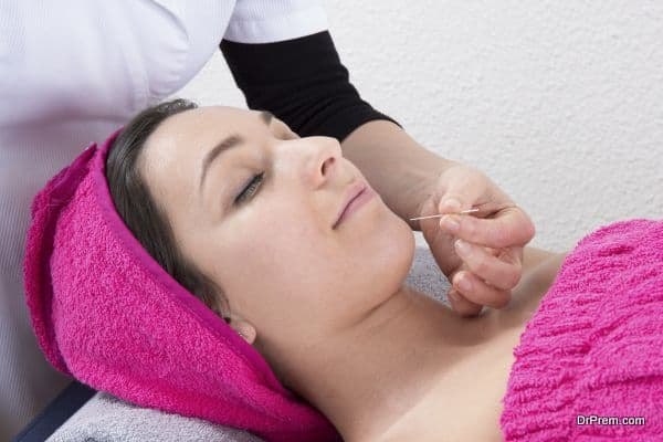 Professional acupuncture therapist placing a needle in the chin of a patient during facial treatment