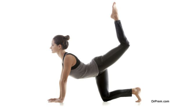 Sporty yoga girl on white background doing exercises for buttocks