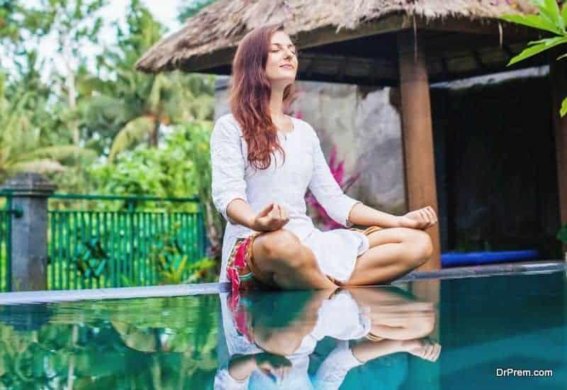 Woman meditating at pool side