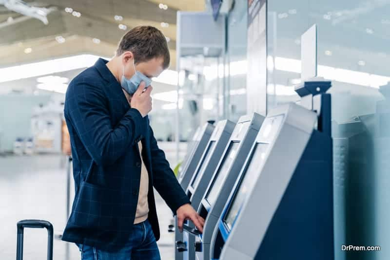man passenger poses near check in desk in airport