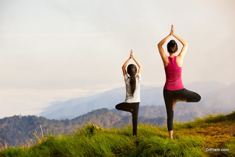Mother and daughter doing yoga at top of mountain