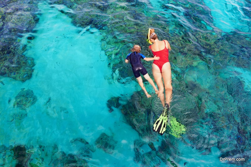 mother, kid in snorkeling mask dive underwater