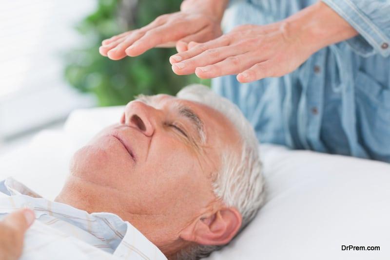 therapist-performing-reiki-over-senior-man