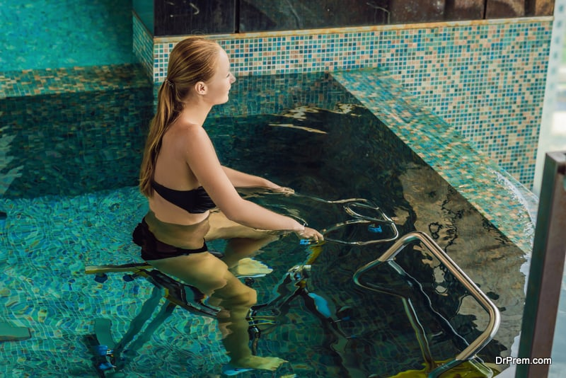 Young woman on bicycle simulator underwater in the pool