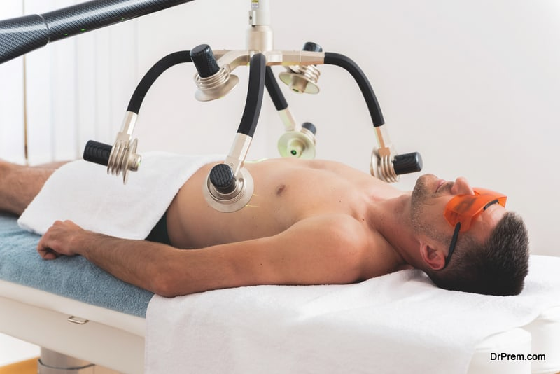 Man having laser treatment for body shaping in aesthetic clinic