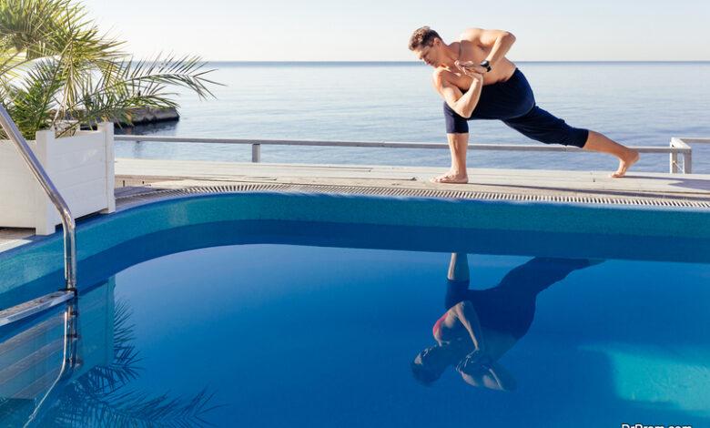 Young attractive man practicing yoga doing Parivrtta Parsvakonasana exercise