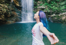 Girl standing with raised arms near the waterfall