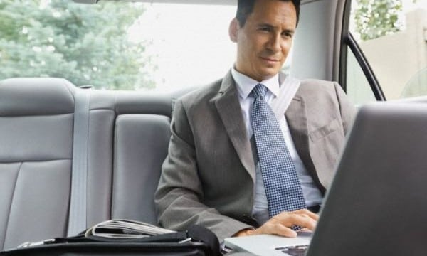 Businessman using laptop in backseat of car