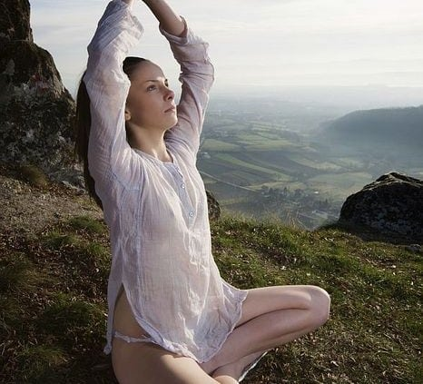"Young woman practicing ""Salute to the Sun"" (Surya Namaskar) yoga on the top of the mountain in the morning"