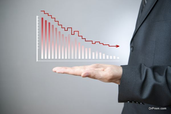 Business concept. Businessman presenting a sustainable decrease development on a bar chart on gray background.