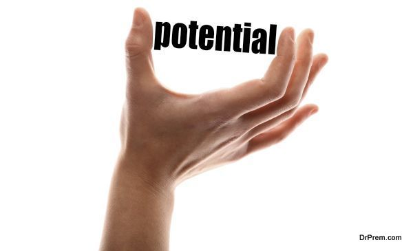 "Color horizontal shot of a of a hand squeezing the word ""potential""."