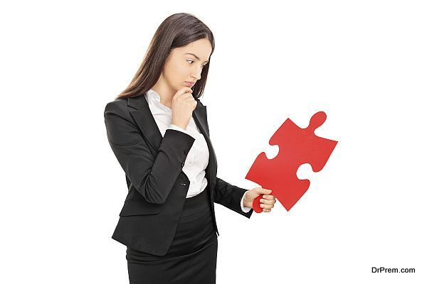 Young brunette businesswoman looking at a big red piece of a puzzle isolated on white background