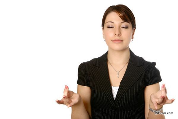 Businesswoman taking a break, concentrating on some yoga breathing exercise as part of a relaxation technique.