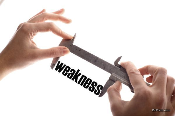 "Color horizontal shot of two hands holding a caliper and measuring the word ""weakness""."