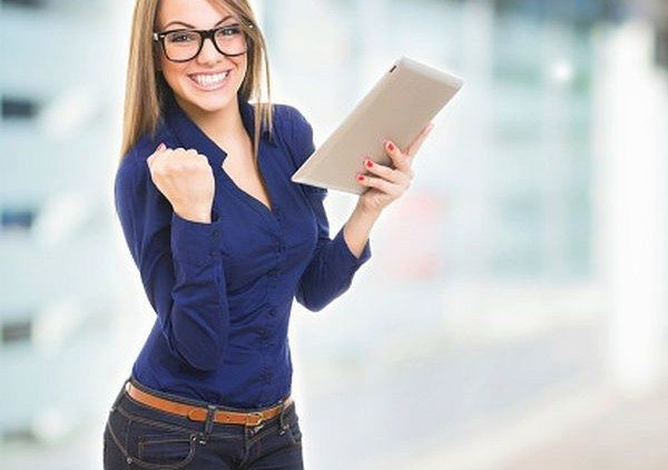 Excited happy young woman wearing glasses with tablet computer