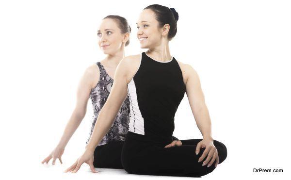 Happy yogi female partners doing asana together, fitness training, yoga practice with partner, sitting, relaxing in pose parivrtta Padmasana, Lotus Position, isolated, white background
